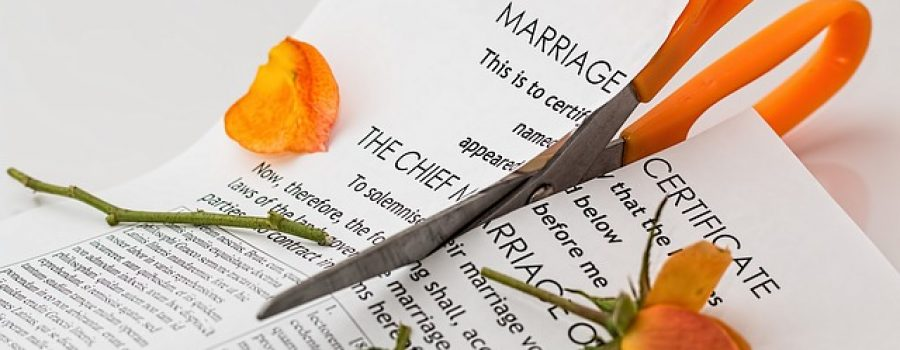 Scissors cutting up marriage certificate